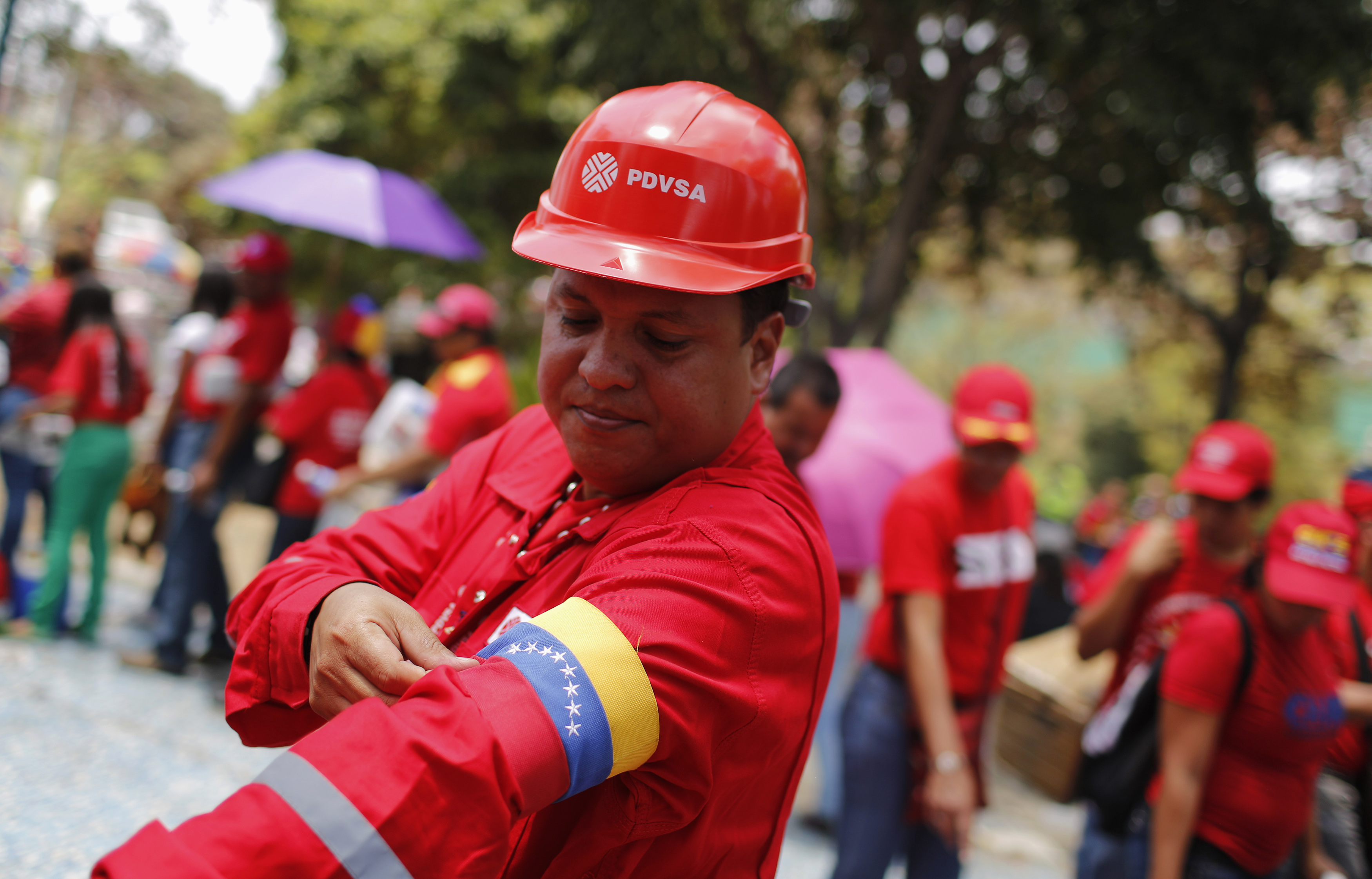 A worker of state-run oil company PDVSA arranges an armband in the colors of Venezuela's flag, at the military academy in Caracas March 10, 2013. Venezuelans of all stripes called on Saturday for a quick presidential election as acting President Nicolas Maduro tries to benefit from an emotional outpouring for his late mentor, Hugo Chavez, and step into his shoes. REUTERS/Tomas Bravo (VENEZUELA - Tags: POLITICS BUSINESS EMPLOYMENT)